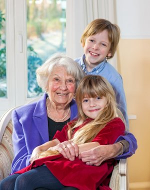 Portrait of an elderly grandmother and her grandchildren sitting in an armchair with the little girl on her lap while her young brother stands behind all looking at the camera with lovely happy smiles. stock vector