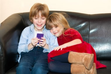 Two young children playing with a mobile phone.