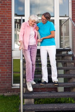 Care assistant helping lady on steps