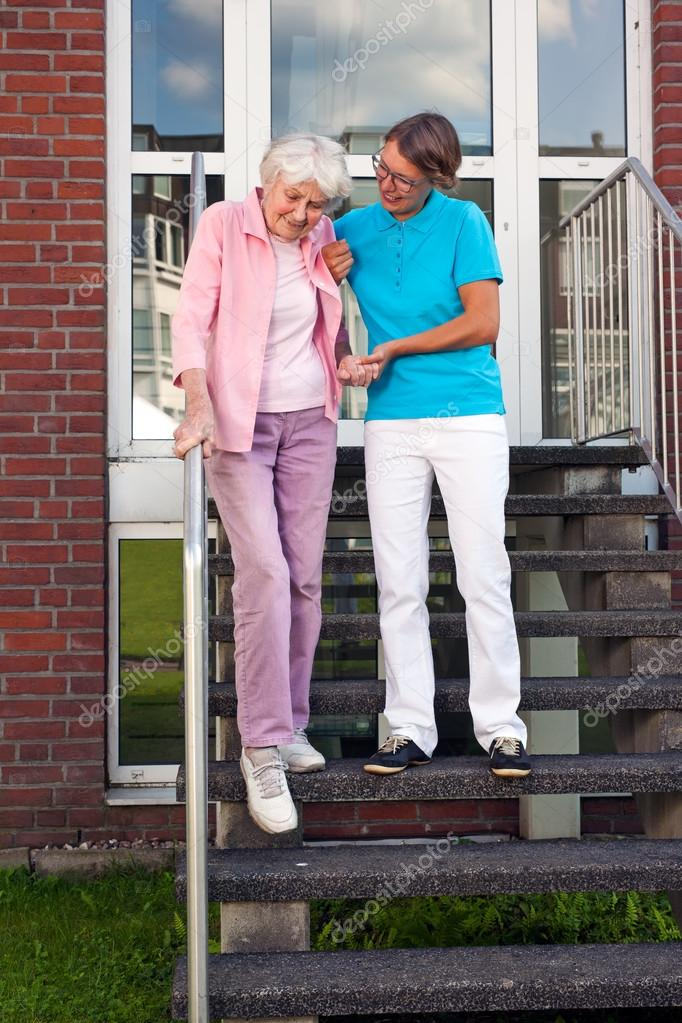 Pflege Assistentin helfende Dame auf Schritte — Stockfoto ...