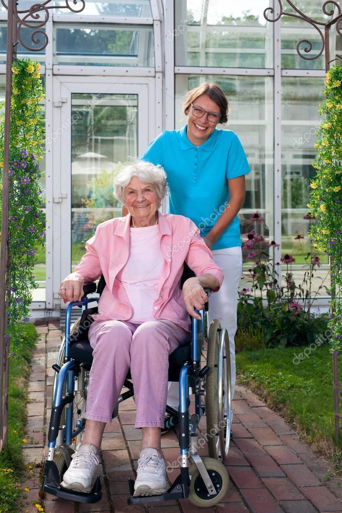 Ältere Dame im Rollstuhl mit Pflege-Assistenten — Stockfoto ...