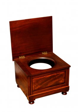 Old toilet with chamber pot an wooden chair