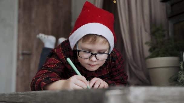 Kaukasischer Junge mit Brille, Neujahrsmütze lügt und schreibt Brief an den Weihnachtsmann