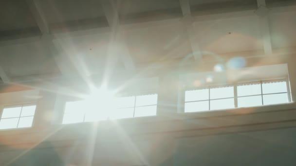 Sluneční paprsky jasně září do oken v blízkosti bílého počítaného stropu s buňkami