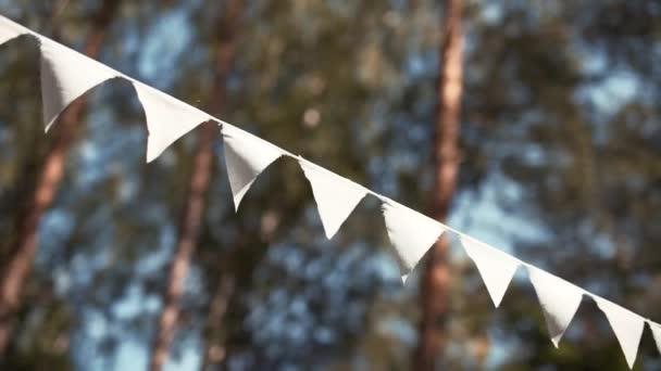 A zászlók koszorúja lóg a kötélen a napsütéses napon