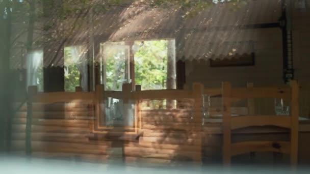 Blick durch Fenster des rustikalen Holzcafés mit Tisch und Stühlen
