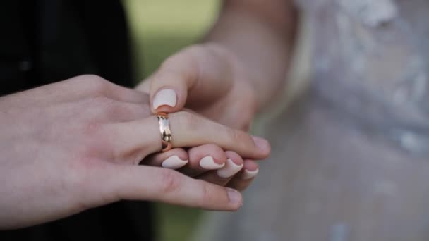 Close-up of girl gently and slowly puts wedding ring on man finger