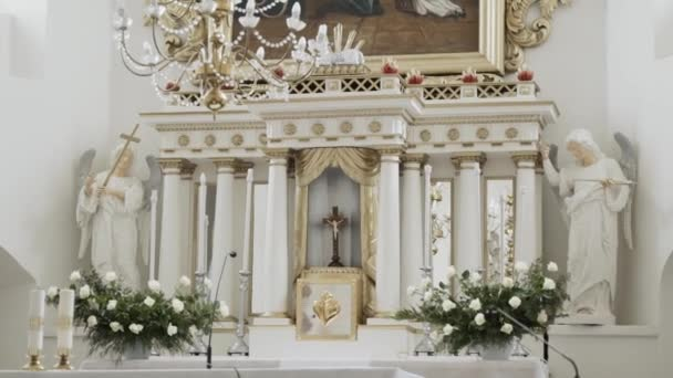 White altar in catholic church decorated with statues of angels and flowers.