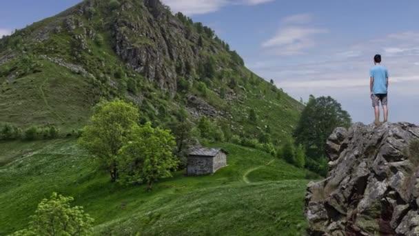 Parallaxe Landschaft eines Jungen, der auf einem Bergsporn steht und auf eine steinerne Hütte blickt, die zwischen Bergen liegt. Kinotag