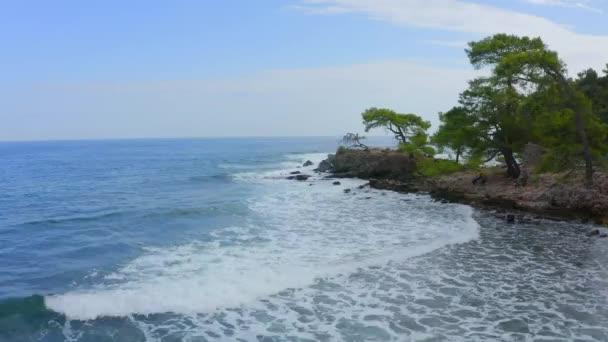 Bei rauer See fliegt die Drohnen-Kamera vom Ufer auf das offene Meer. Ein wunderbarer blauer Himmel, eine Leerstelle zum Schreiben oder Setzen eines Logos. Der Küstenstreifen besteht aus Wäldern und Bäumen. Kamerafahrt zur See