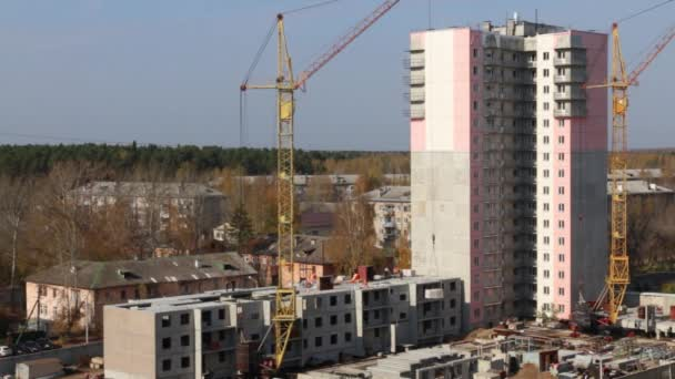Staveniště se dvěma pracovní jeřábů a součástí panelové budovy