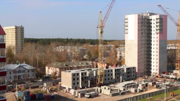 Staveniště se dvěma jeřáby a část panelové budovy