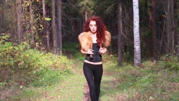 Donna abbastanza giovane con pelliccia passeggiate nella foresta di autunno al giorno pieno di sole