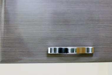 Shiny chrome handle on brown wooden door on cupboard. Close up