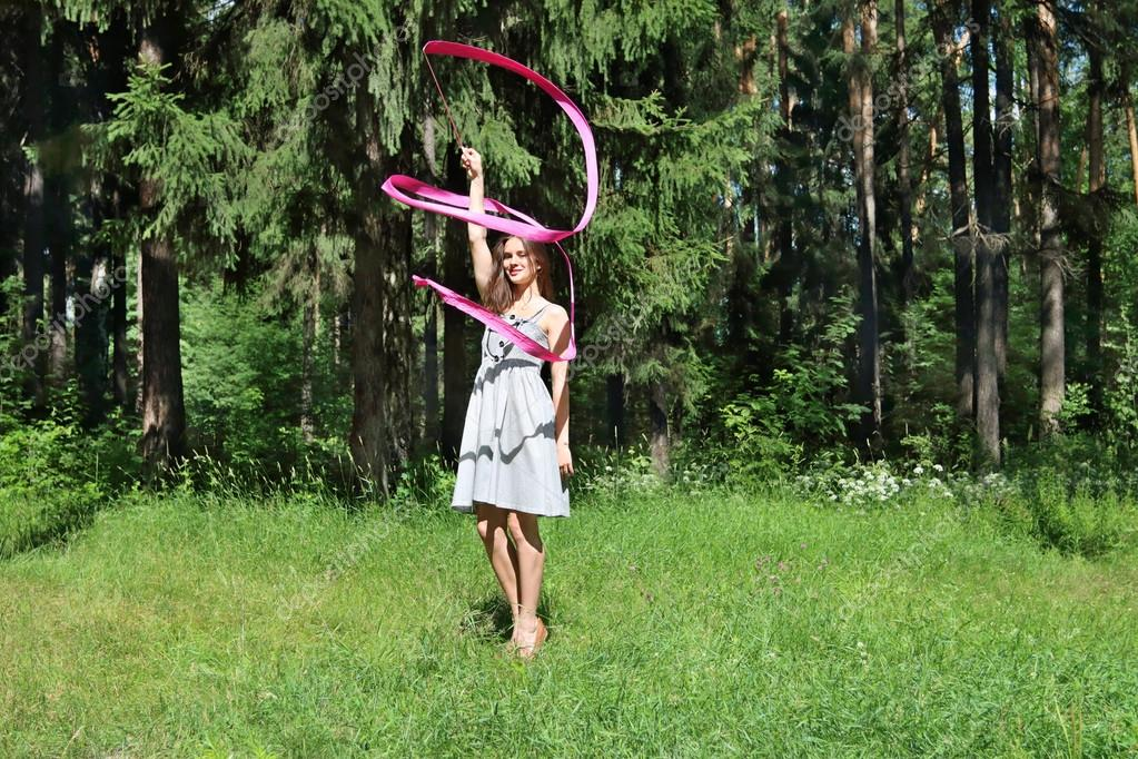 Beautiful girl in dress is engaged in rhythmic gymnastics with r