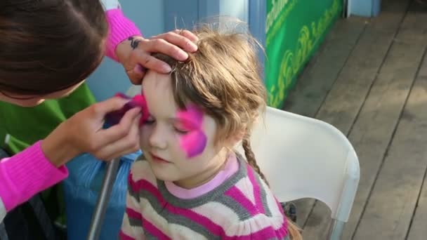 Woman paints pink butterfly on face of little cute girl outdoor