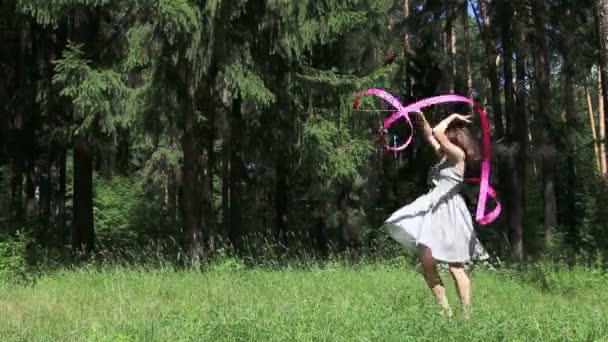 Young woman in dress dances with pink ribbon in summer forest