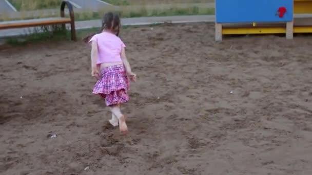 Happy little bos dívka v růžovém běží na hřišti v létě
