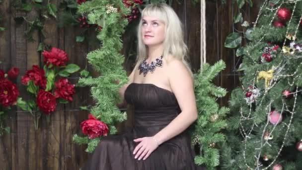 schöne junge Frau sitzt auf Schaukel und blickt in der Nähe des Weihnachtsbaums auf
