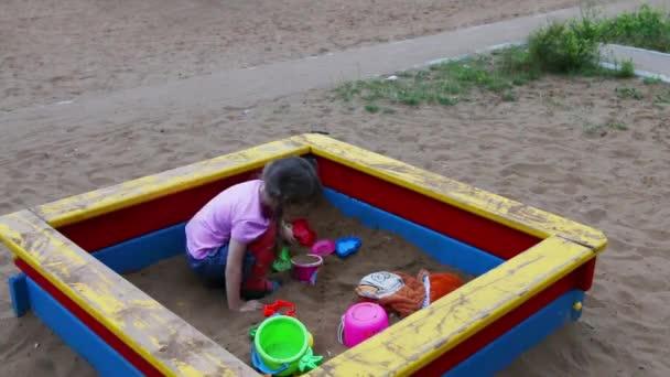 Kislány ül és játszik a játékokkal, homokozó, játszótér