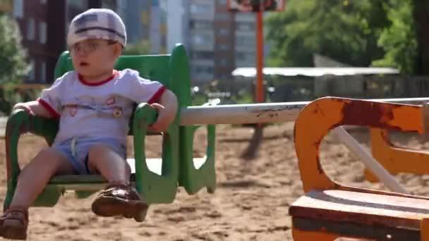 Malý hezký chlapec v brýlích jezdí na kolotoč na hřišti