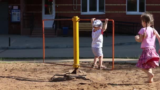 Mädchen und Junge wirbeln auf Spielplatz