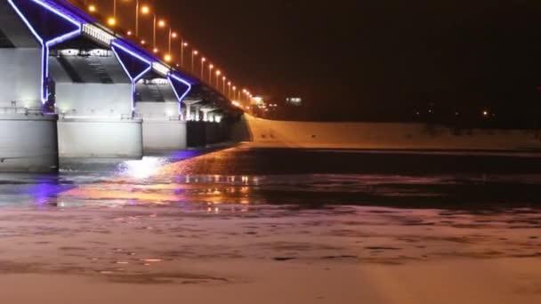 Night illuminated bridge and river with ice at winter night