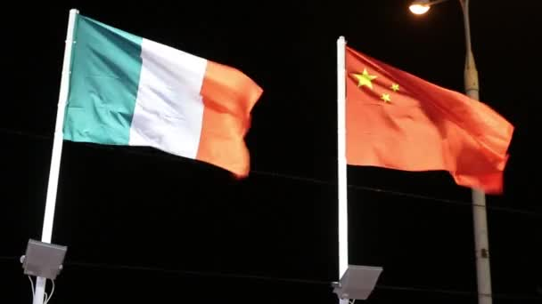 Flags of Italy and China with illumination on wind at dark night