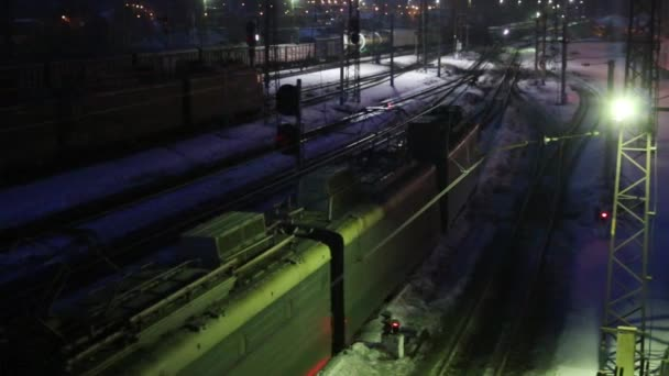 Long freight train moves on railway at winter night