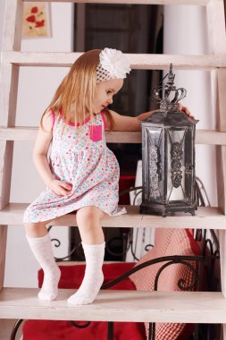 Little cute blond girl in dress sitting on wooden stairs with wi