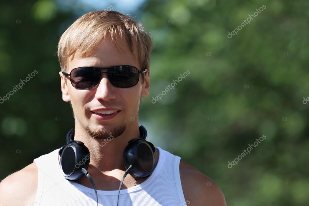 Man in sunglasses and headphones in park with green trees
