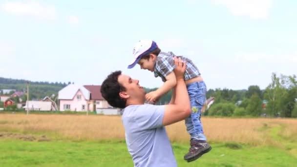 Šťastný otec hraje s jeho malým synem na zelené louce