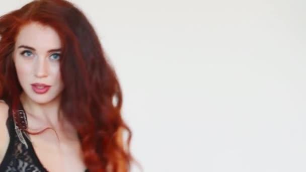 Žena s červenými vlasy tance v bílém studio