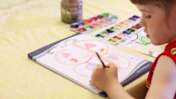 Kis lány festés pillangó notebook asztalnál. Közelről