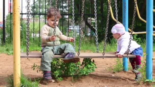 Little cute girl and boy are playing on swings at playground