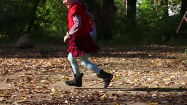 Little girl and boy running after pigeons in autumn day