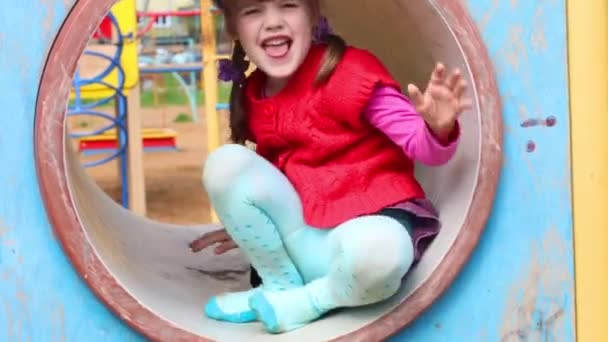 Little beautiful girl sitting in tube on playground