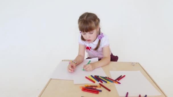 Közelkép a kis lány festék a papírt, ceruzát stúdió