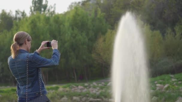Ein Mädchen mittleren Alters steht mit dem Rücken zur Kamera und fotografiert mit ihrem Handy einen Springbrunnen im Park. Schöne Orte der Natur. Foto zur Erinnerung.