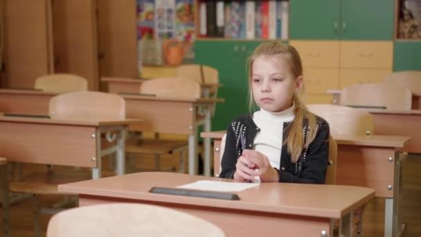 Egy általános iskolás lány ül egy asztalnál, és nagyon aggódik a vizsga miatt. Szorongás a vizsga alatt. Valódi érzések.