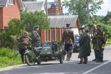 Military retro motorcycle and a group of reenactors on the road, the 3rd international meeting of