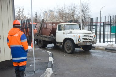 The old white truck ZIL with snow enters into a snow melting point in Moscow
