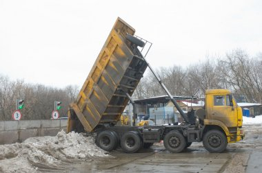 Unloading dirty snow from the body of the truck KAMAZ in negotable on snow-melting point, Moscow