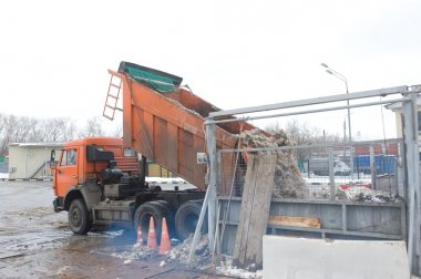 Unloading the dirty snow of the body orange truck in negotable on snow-melting point