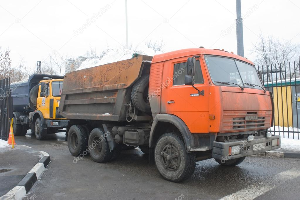 Orange dump truck KAMAZ at the entrance to the snow melting point Moscow