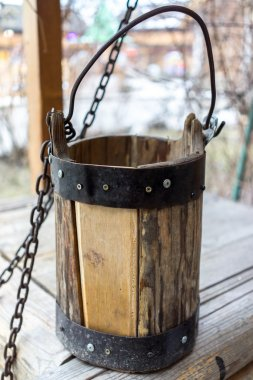 Detail of old draw well with wooden bucket on a metal chain close up view in Izmailovo Kremlin, Moscow, Russia