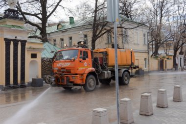MOSCOW, RUSSIA - APRIL 7, 2015: Red KAMAZ 53605 watering and cleaning machines at the city street.