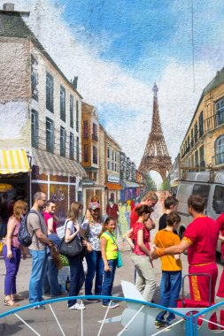 MOSCOW, RUSSIA - JUNE 07, 2015: people are walking near the wall with street art graffiti of Paris street and Eiffel tower