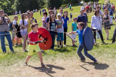 MOSCOW, RUSSIA - JUNE 07, 2015: two boys fighting with a wooden swords and shields playing knights on the park in a sunny day in Moscow