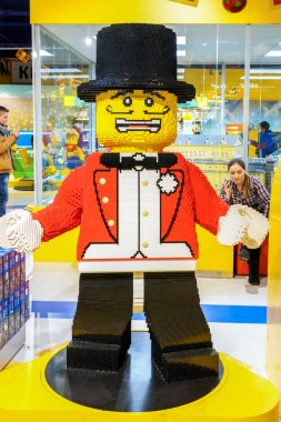 MOSCOW, RUSSIA - DECEMBER 11, 2015: man sculpture in red tail-coat and black cylinder hat made by Lego blocks in Central Children's Store on Lubyanka greeting visitors at the entrance